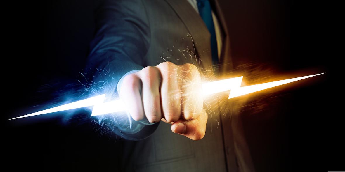 Hand holds lightning bolt